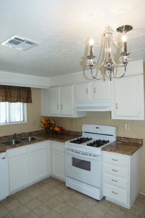 new stove, countertops and light fixture in kitchen